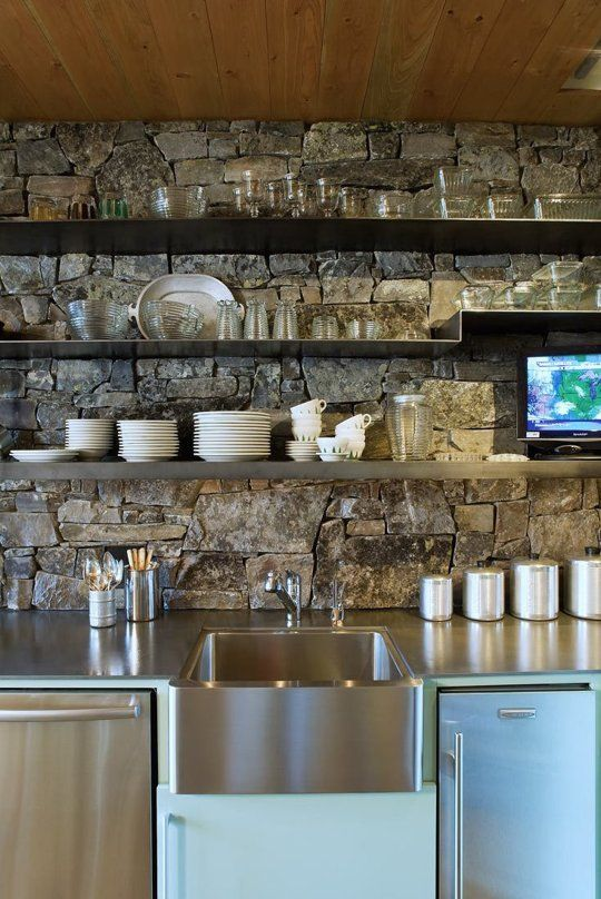 weathered stone accent wall in organic modern kitchen